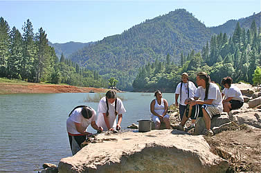 photo of people outdoors on a rock by a large lake in the mountains. they are making tea