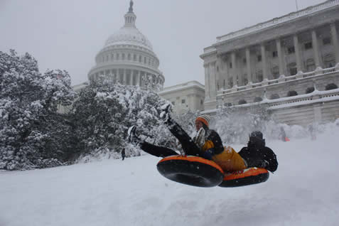 photo of people sledding on an innertube in front of the US capitol