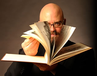 photo of a man fanning the pages of a book