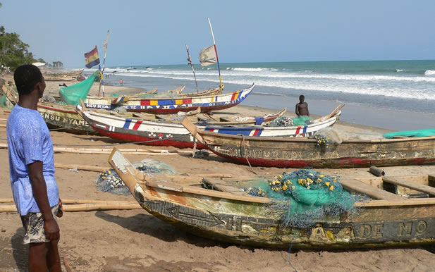 photo of a beach with brightly painted dugout canoes