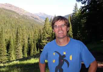 photo of a smiling man in a meadow fringed by pines in sunlight