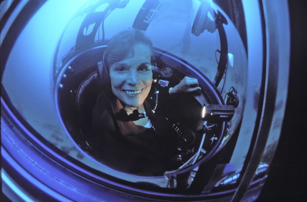 photo of a woman smiling in an underwater habitat or hard-suit