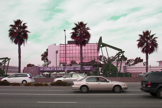 photo artwork depicting a cafe, office building, and palm trees, oil pumpjack adjacent
