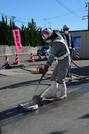 photo of workers wearing protective gear using machinery to clean a flat surface