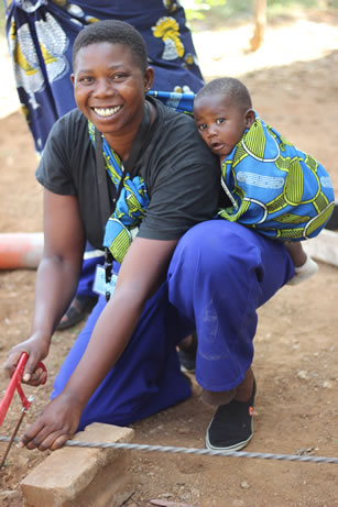 photo of a woman working, she is carrying a baby on her back and smiling