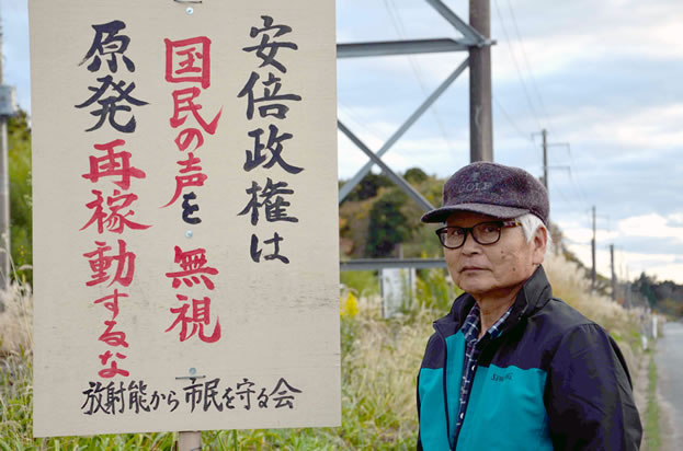 photo of a man standing outside under powerlines, a sign in Japanese hanging near him