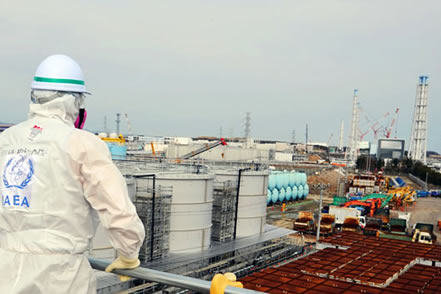 photo of a worker in an anti-contamination suit looking out over an industrial site near the sea