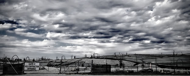 photo of a capped landfill under a threatening sky