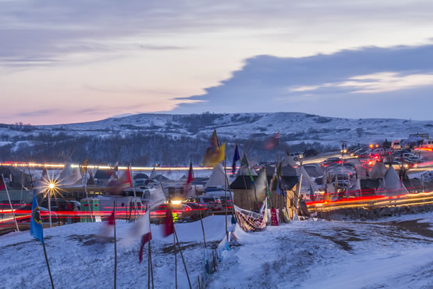photo of a snowy camp in twilight, colorful flags and teepees evident
