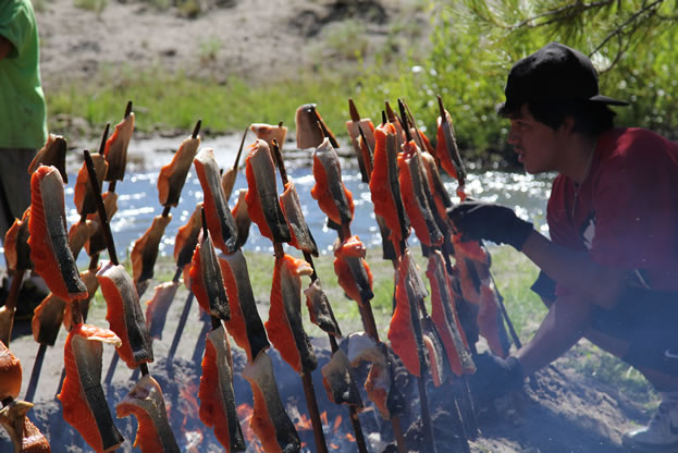 photo of salmon meat cooking on spikes