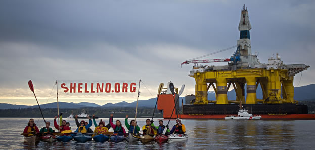 photo of kayakers near an oil platform holding a sign that reads shellnoorg