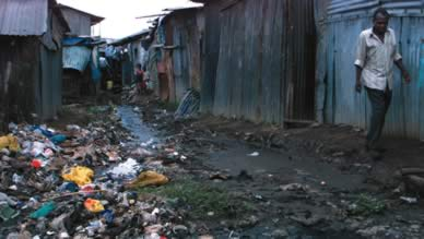 A Kenyan slum dweller avoids trash and sewage as he walks in the Nairobi slum of Kibera. -Reuters photo