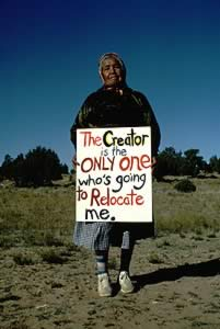 Elder woman holding sign reading