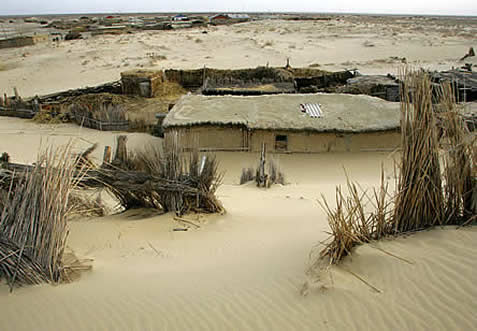 photo of a dwelling in drifted sand, ruins around