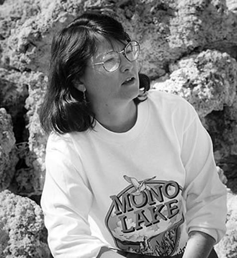photo of a woman wearing a mono lake t-shirt, sitting near tufa towers at that site