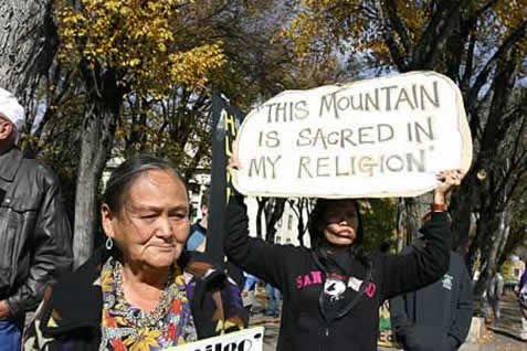 photo of demonstrators in a forest, one holding a sign that reads 'this mountain is sacred in my religion'