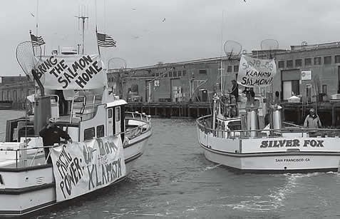 photo of boats in a demonstration, bearing signs 'bring the salmon home' and 'undam the klamath'