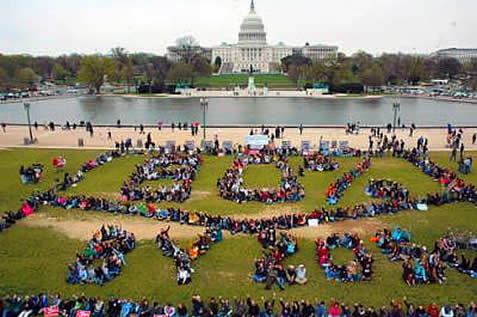 photo of demonstrators outside the US capitol, arranged into a human banner reading '80% by 2050'