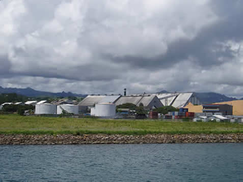 photo of a series of buildings in a coastal field, low tropical stormclouds overhead