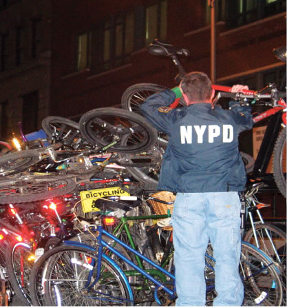 photo of a police officer piling bikes together