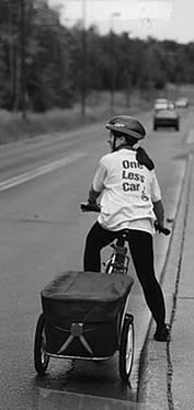 photo of a woman riding a bicycle with a trailer, her shirt reads 'one less car'