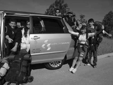 photo of young people in camping gear showing off a van