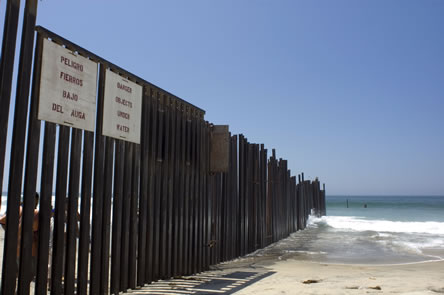 photo of a fence perpendicular to a beach, the fence continuing into the sea; sign on fence in Spanish and English: danger, objects under water