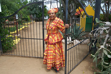 photo of a woman in colorful clothes opening a gate