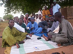 photo of a group of people in traditonal dress sitting on a blanket in an arid land