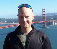 photo of a bald man standing with the Golden Gate Bridge in the background