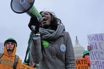 photo of people wearing green hardhats at a demonstration; US Capitol building in the background, young woman with a megaphone in foreground