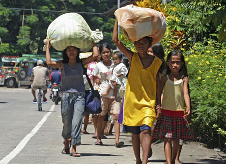 photo of people walking on an urban street carrying large bundles on their heads
