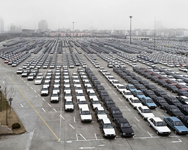 photo of a vast lot parked with similar cars arranged in rows by color; hazy urban towers lie in the background