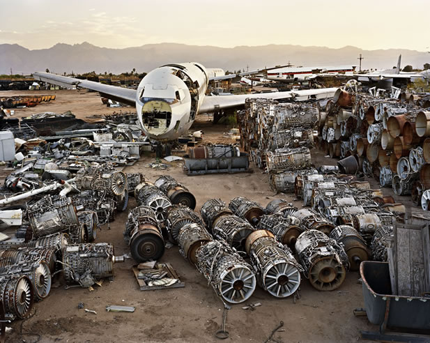 photo of a scrapyard in a desert plain, parts of a broken jet including many turbines in foreground, sharp peaks behind