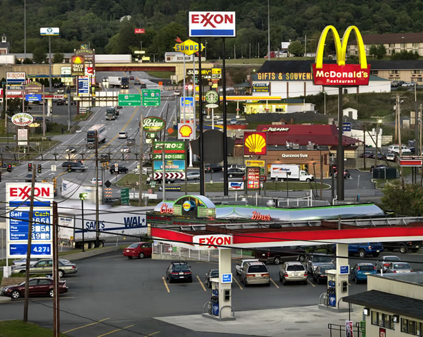 photo of a streetcorner riot of logos, overhead wires, and traffic; gas stations and fast food franchises dominate