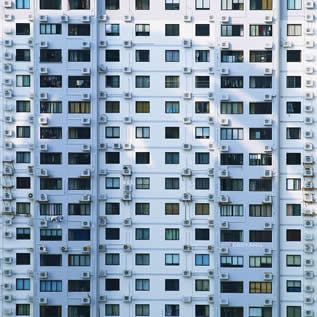 photo of the side of a tall building, windows covered with AC units
