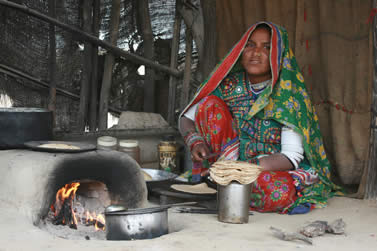 photo of a woman in multicolored clothing using an oven to cook flatbread