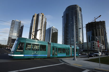 photo of a light-rail train in a shiny city