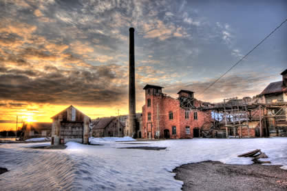 photo of a series of dilapidated buildings at a minesite in the snow at sunset