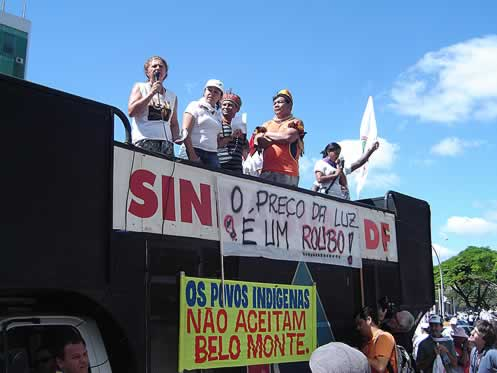 photo of demonstrators on a stage, banners in Portugese
