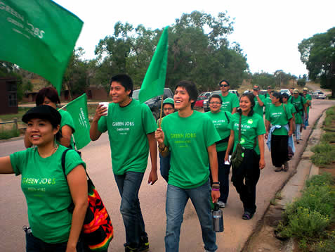 people walking together wearing green jobs shirts and carrying flags. they are smiling