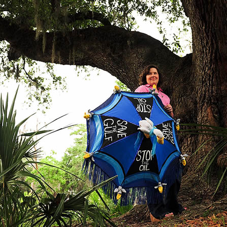 photo of a woman in a cypress woodland, holding an umbrella with 'save the gulf' written on it