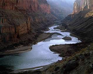 photo of a river flowing through a deep canyon, sun slanting across the top