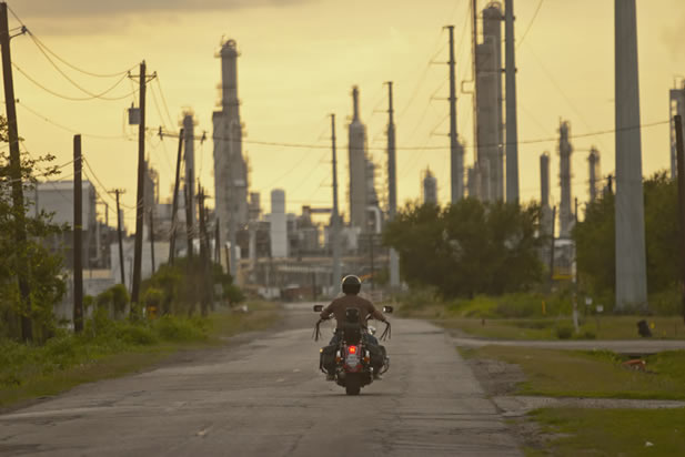 photo of a motorcyclist riding along a curbless street into a cluster of fractionation towers at a refinery. The sky is an unhealthy color.