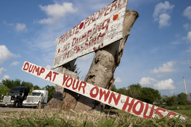 photo of a handpainted sign on a stump, words, private property, dump at your own house