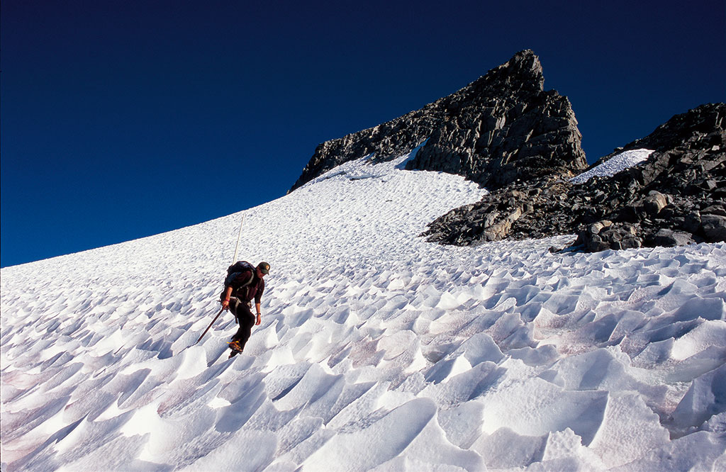 photo of a man with technical gear traversing ice in an alpine environment