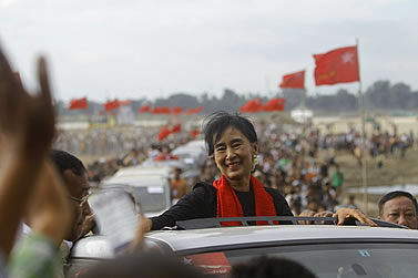 photo of a woman smiling, riding in a motorcade