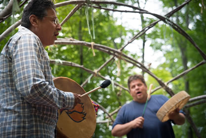photo of two men playing handmade drums and singing in a forest