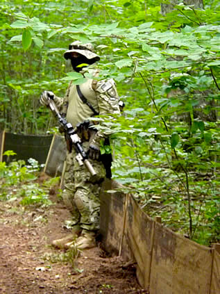 photo of a man in military garb holding a big weapon in a forest