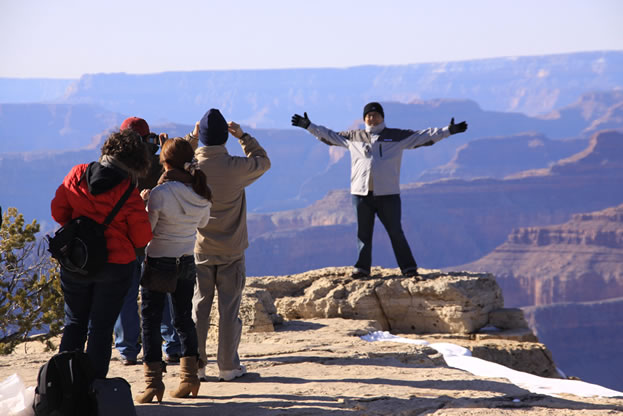 photo of a family taking pictures at the rim of a canyon